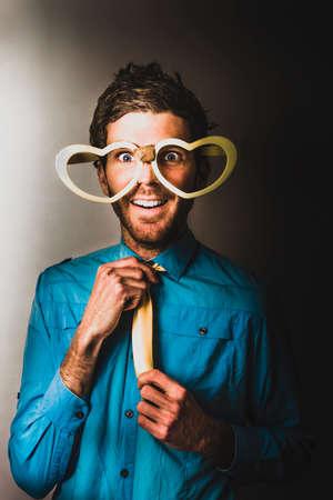 PrEP: Love struck Valentine`s Day nerd wearing heart eyeglasses in prep for the approach. Dating dork Stock Photo