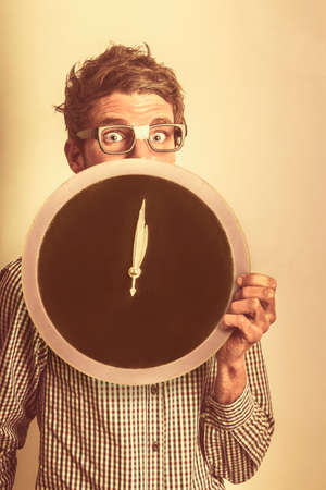 overdue: Accounting and bookkeeping nerd holding large copyspace clock on vintage office wall. Tax return overdue