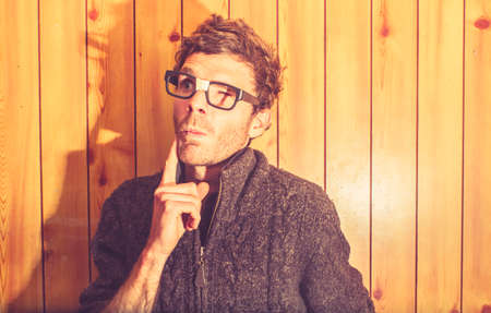 oddball: Retro style portrait of a nerd man in thick woolen jumper thinking on wooden office interior. Smart Ideas Stock Photo
