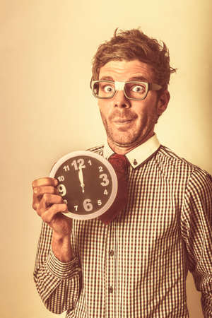 clerical: Humorous office clerical staff member holding small round clock with look of alarm. Deadline looming