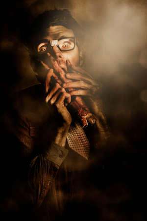 devouring: Geeky zombie gasping in fog filled moonlight when devouring a bloody hand in the macabre madness of fright night