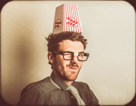 funny movies: Retro photograph of a funny movie critic wearing popcorn knowledge hat. Film nerds Stock Photo