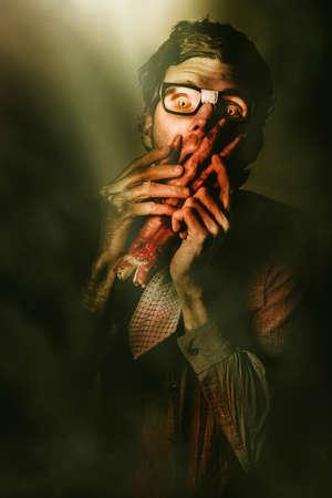 revenge: Dark dramatic horror portrait of a evil halloween geek eating human limb in the dark of twilight. Revenge of the nerd