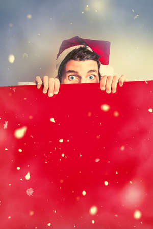 northpole: Surprised santa elf holding red christmas board in a creative winter scene of falling snow. Merry xmas advert Stock Photo