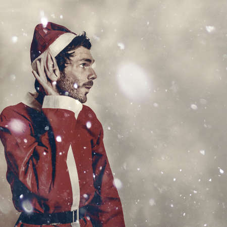 christmas costume: Magical holiday portrait of a christmas elf hearing in the new year celebrations under the fall of snowflakes. Sound of seasonal joy