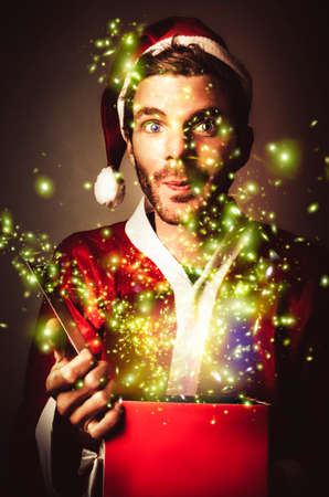 christmas gift: Creative portrait of a gift wrapping santa holding open red box with magical sparks of joy. Fantastic christmas presents