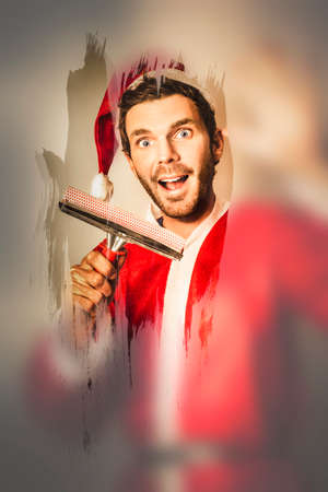 man cleaning: Christmas elf cleaning window frost at north pole with happy expression. Helping santa with x-mas holiday preparation Stock Photo
