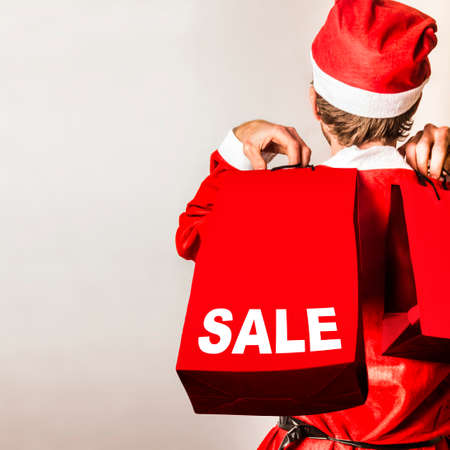 christmas shopping bag: Cute behind view of a little Santa helper at boxing day sale with red hat and shopping gift bags. After christmas sales Stock Photo