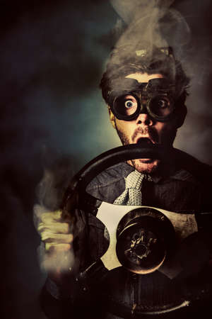 nerd: Dark creative concept portrait of a nerd business man holding steaming auto wheel during a fast pace race competition. Street racer Stock Photo