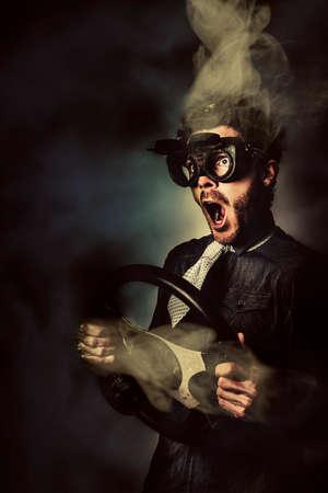 gente loca: Retrato divertido de un conductor masculino loco con la cabeza de fumar y el volante independiente. Carreras de coches Speed