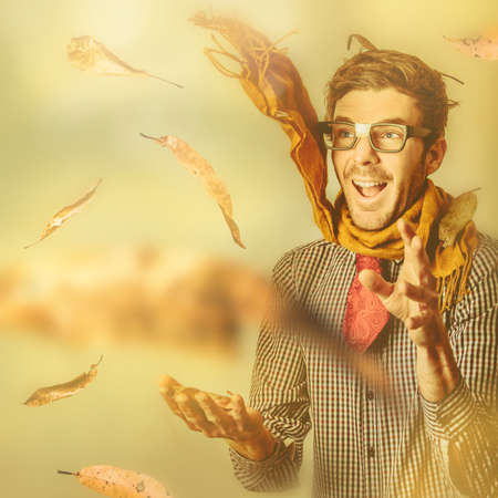 wind blown: Creative portrait of a happy nerd with wind blown scarf embracing his inner child while playing with leaves in the fall of a golden autumn Stock Photo