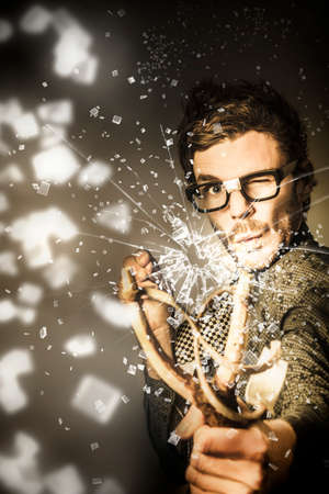 best practice: Creative concept art of a nerd business man taking best practice aim with slingshot in a smash hit of innovation. Target market success Stock Photo