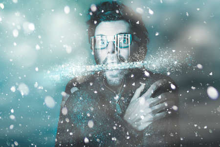 freeze: Ice cold winter art of a man holding explosive thermometer in shivering jaw while in a freeze of snow and frost from a blizzard of falling white ice. Temperature below freezing Stock Photo