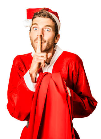 Isolated secret santa whispering a gesture of quiet while sneaking around with silent night christmas presents over white background Stock Photo