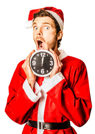 Shocked man in santa suit holding clock with a minute to spare till midnight. Countdown to christmas time coming soon