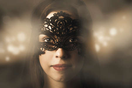 masquerade ball: Mystery and fantasy concept on the face of a beauty model wearing dark black venetian carnival mask at new year party celebration on magic light background. Masquerade ball woman Stock Photo