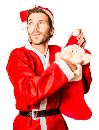 stuffer: Man in santa costume stuffing holiday sock while on the lookout for seasonal fillings. Stocking up on Christmas gifts