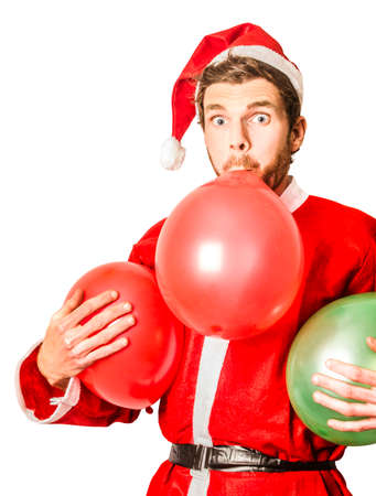 santa suit: Funny man in santa suit blowing up red and green xmas balloons with humorous expression. Christmas party planner