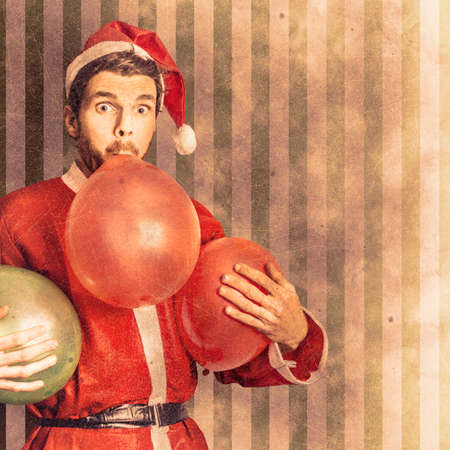 decorate: Vintage textured christmas card concept on a santa man blowing up party balloon in preparation for a happy holiday event. Xmas copyspace celebrations