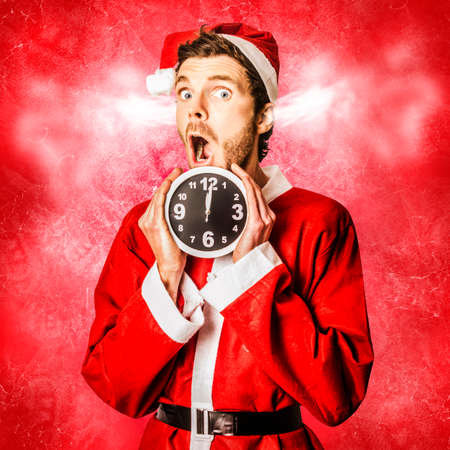 clock: Funny xmas concept of a surprised santa in a expression of crazy stress while holding ticking time clock. Christmas mad rush