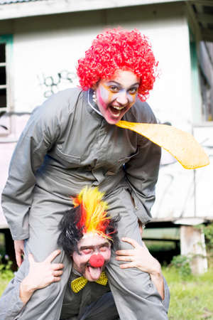 clowning: A Balancing Act Sees A Clown Riding On Another Clowns Back In A Playful Display Of Clowning Around Stock Photo