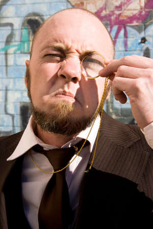 squint: Vision Impared Squinting Monocle Man Looks Though Monicle Stock Photo