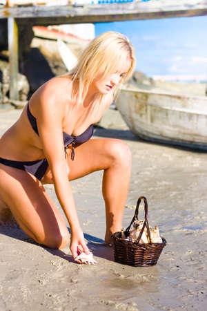 mujer arrodillada: Mujer linda Ambiental Rodillas hacia abajo en un Sunshine Beach ubicación de recogida conchas de mar de la costa del océano hora de descubrir la belleza de la naturaleza