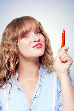 garabatos: Estudiante femenino sonriente apuntando hacia arriba al espacio en blanco copia educación con un lápiz en un garabato tu anuncio aquí conceptual