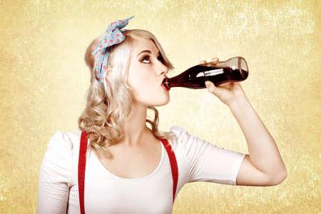 gaseosas: bebida de la muchacha hermosa rubia pinup beber refresco en la tienda de dulces de la vendimia Foto de archivo
