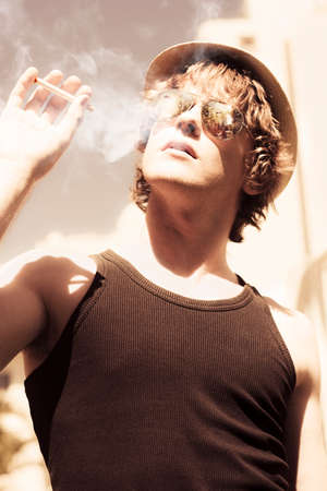 puffing: Low angle artistically toned image of a trendy young person in hat and sunglasses puffing on a smoke outdoors
