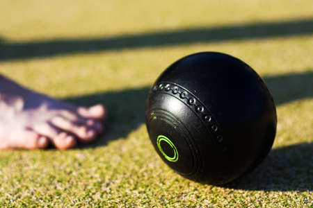 bowl game: A Bare Foot Bowler Puts His Best Foot Forward, Image Consisting Of A Black Lawn Bowls Ball With An Out Of Focus Foot To Its Left.
