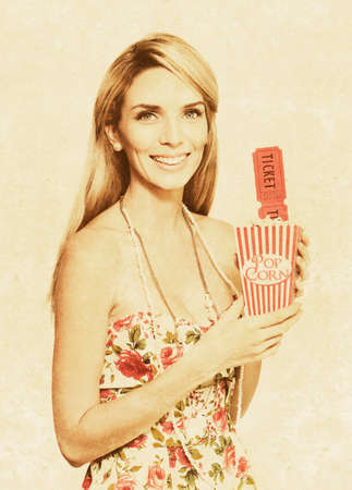 olden: Faded And Textured Image Of A Vintage Woman With Smile, Pop Corn And Movie Tickets In A Olden Day Drive In And Movie Theatre Concept