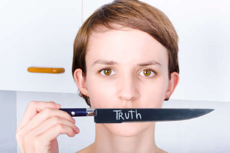 rectify: Face of a stern woman cutting the silence when making a sharp point of TRUTH with a kitchen knife in a depiction of spreading fact over false food beliefs Stock Photo