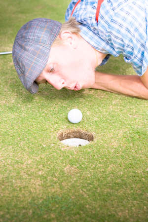attempting: Desperate And Frantic Golfer Attempting To Inch His Green Ball Closer To The Golfing Hole By Blowing On It In A Humorous And Funny Golf Cheating Concept Stock Photo