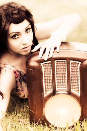 Vintage Woman Laying In The Sun During Summer Wearing Fifties Fashion While Holding A Retro Radio With One Hand In A Old Communication And Entertainment Concept Imagens