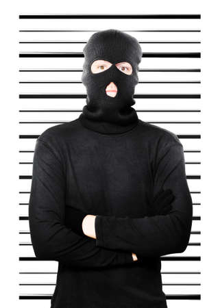 apprehended: Mugshot of a busted thief caught in the act of petty larceny standing dejectedly in front of a police background as he is apprehended yet again as a repeat offender Stock Photo