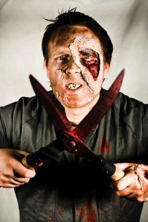 supernatural power: Death By Zombie. An evil decaying zombie holding a pair of bloodied garden shears with blades open.