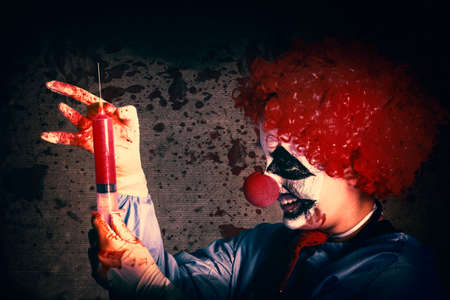 clowning: Scary clown holding large injection needle filled with human vaccine test trials. Bad medicine