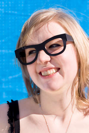 mischievous: Mischievous Looking Woman Beams In A Cheeky Grin Expression While Wearing Fake Glasses In Front Of A Blue Background Stock Photo
