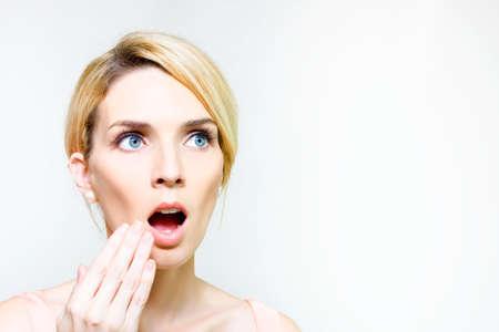 preocupacion: Pretty blonde muestra sorpresa y choque con la mano para hacer frente al escuchar sorprendente información o noticias impactantes Foto de archivo