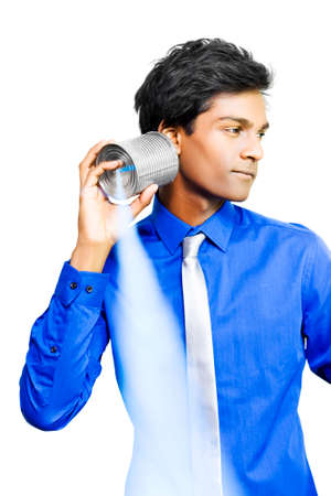 tin can telephone: Young Asian business man listens carefully to an old-fashioned tin can telephone which transmits sound by vibration as he mulls over a new invention