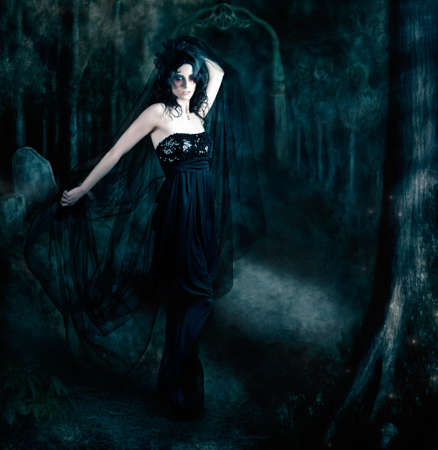black shadows: Moody atmospheric portrait of an elegant mysterious woman posing in a black evening gown amongst the shadows of darkness Stock Photo