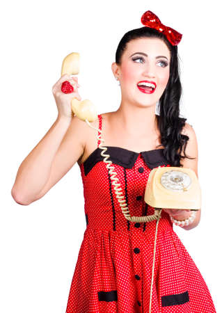 turn over: Funny pin-up woman talking on a retro turn dial phone over white background Stock Photo
