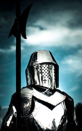 muddle: Middle Ages Portrait Of A Medieval Knight In Silver Shining Armor Holding Weapon Against A Blue Sky
