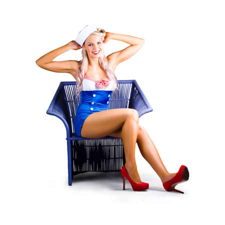 cane chair: Isolated cute blond pinup girl in a military blue navy uniform, on white background Stock Photo