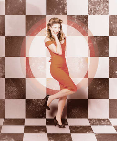 50s fashion: Creative vintage portrait of a beautiful pin-up girl striking a pose on circular dot background inside checker tile diner. 50s fashion glam