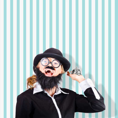 summons: Humorous photo of a dodgy salesman ready to assist when holding a silver service hotel bell on aqua retro striped background Stock Photo