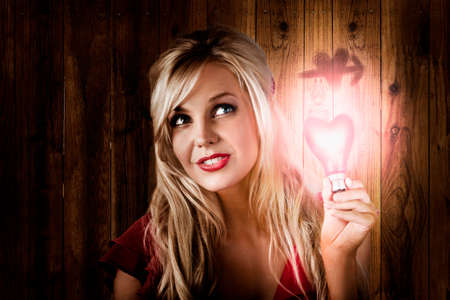 lost love: Hopeful beautiful blond woman holding heart shape light bulb when searching for her long lost love