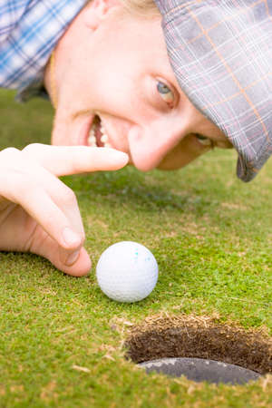 bending down: Focus On The Head Of A Mischievous Golfer Bending Down On A Golfing Green To Give The Golf Ball A Helping Hand To The Hole In A Cheeky Sports Victory Stock Photo
