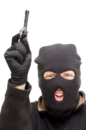 malandros: Estudio Imagen De Un Balaclava Wearing Bandit apuntando su arma Skywards Durante Un Atraco Armado Foto de archivo